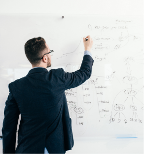 young-attractive-dark-haired-man-glasses-is-writing-business-plan-whiteboard-he-wears-blue-shirt-dark-jacket-view-from-back